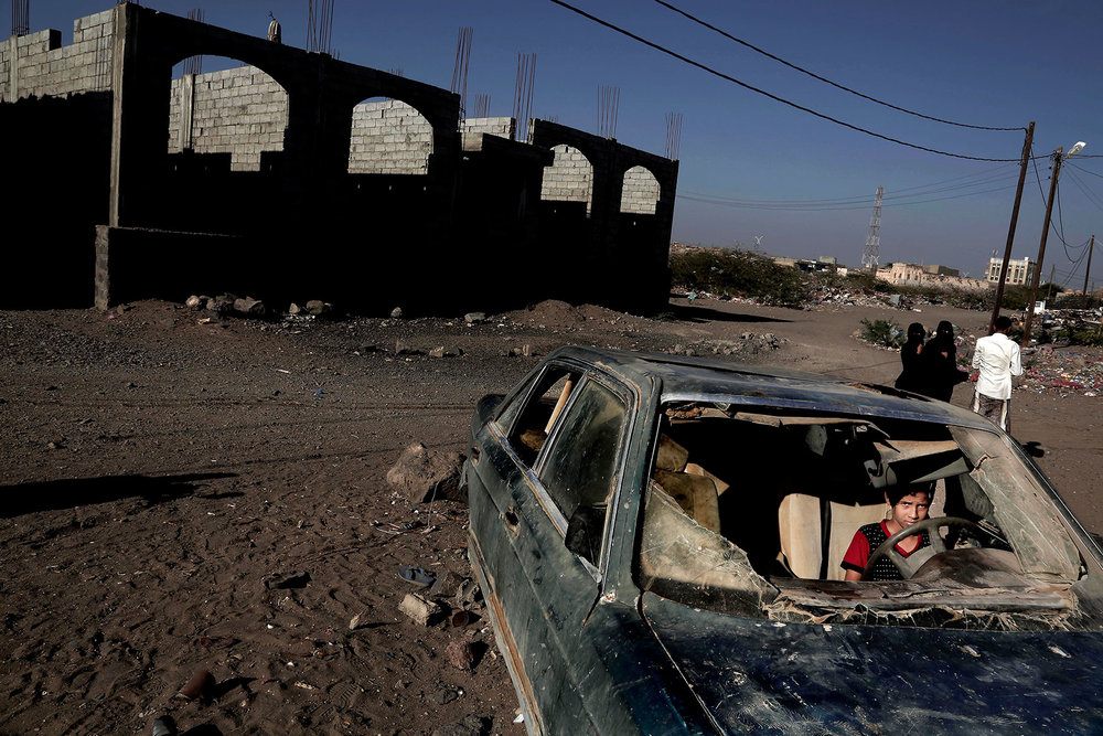 In this Feb. 10, 2018 photo, a boy sits in a damages car due to the on-going three year conflict in Mocha, Yemen. (AP Photo/Nariman El-Mofty)