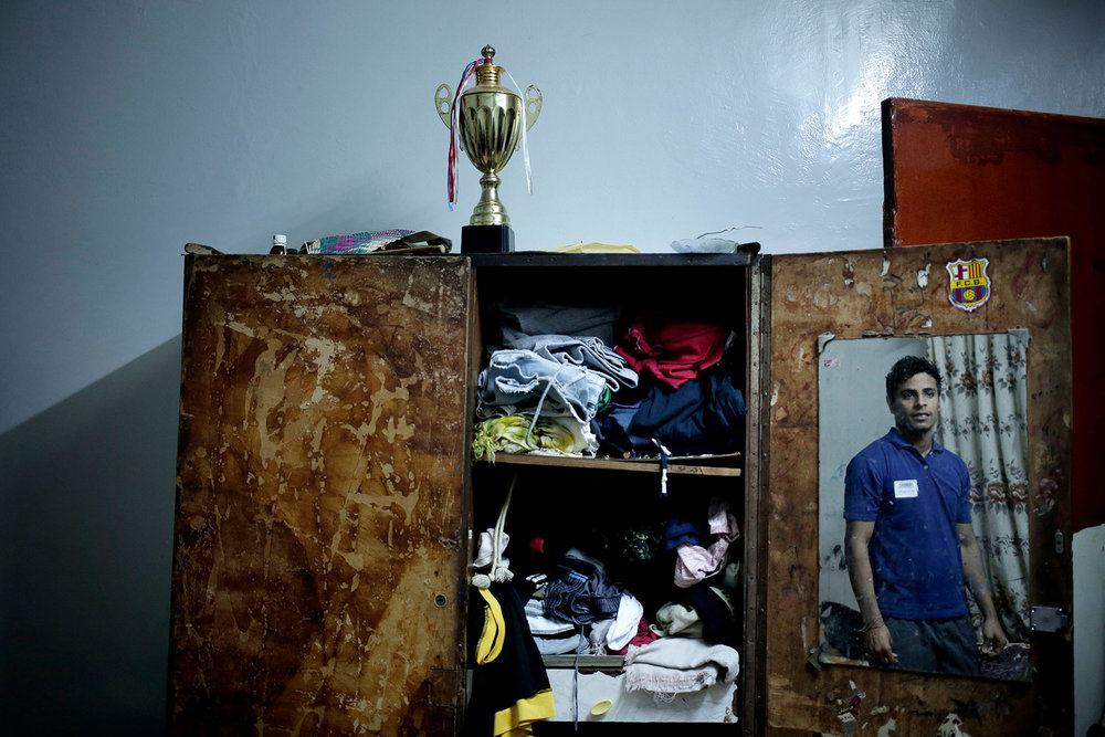 In this Feb. 17, 2018 photo, 21 year-old Ahmed Saleh, who fought during the '2015 battle of Aden' looks at himself in the mirror in his bedroom, at his home in Aden, Yemen. (AP Photo/Nariman El-Mofty)