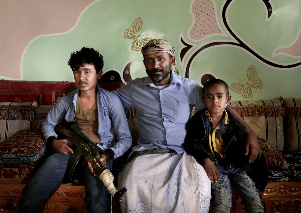 "In this Feb. 12, 2018 photo, Ahmed al-Kawkabani, center, leader of the southern resistance unit in Hodeida poses for photo with his 16-year old son Shaeeb, left, and his 8-year old Abdullah, at their home in al-Khoukha, Yemen. ""My son wants to join me but I try to tell him to focus on school. He finishes school changes from his uniform and takes his rifle,"" the father said. (AP Photo/Nariman El-Mofty)"