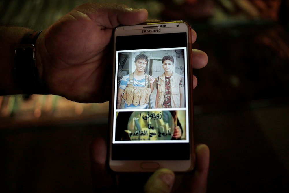 "This Feb. 17, 2018 photo, shows a mobile photo of then 18-year old Ahmed Saleh, left, with his friend during the '2015 battle of Aden' and Arabic that reads, ""marry me or I will go with Al Qaida,"" in Aden, Yemen. (AP Photo/Nariman El-Mofty)"