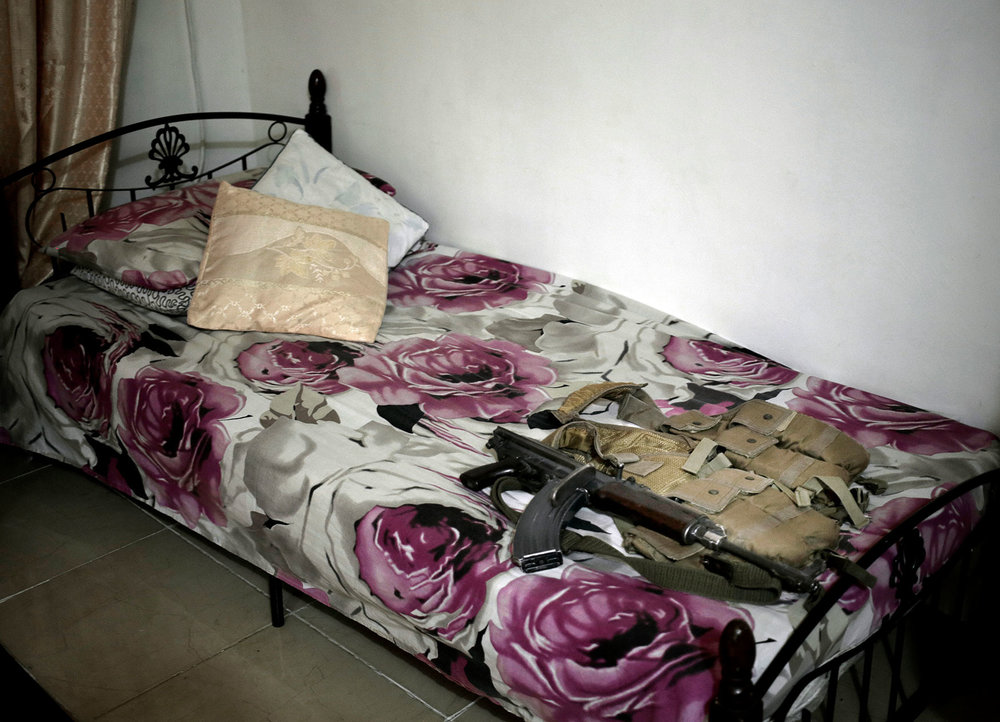 "In this Feb. 17, 2018 photo, shows the rifle and body armor used by Osama Ahmed, during the '2015 battle of Aden' on his bed in his room, at his home in Aden, Yemen. ""As a Yemeni citizen you can't leave the country - we are listed as terrorists - we had dreams and wanted to do things with our lives. There are no opportunity for the youth, we just want to live in peace without violence,"" he said. (AP Photo/Nariman El-Mofty) in Aden, Yemen. (AP Photo/Nariman El-Mofty)"
