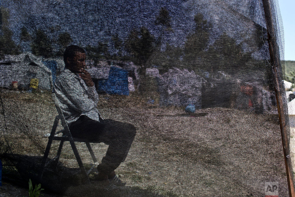 Hasan, no other name given, from Deir ez-Zor in Syria, who arrived in Greece six months ago, sits behind the net of his tent at a makeshift camp outside the official camp of Moria at the island of Lesbos on Wednesday, May 2, 2018. (AP Photo/Petros Giannakouris)