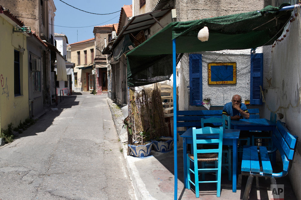 A man sits on a chair outside a closed coffee shop in the town of Mytilene on the northeastern Aegean island of Lesbos, Greece on Thursday, May 3, 2018. (AP Photo/Petros Giannakouris)
