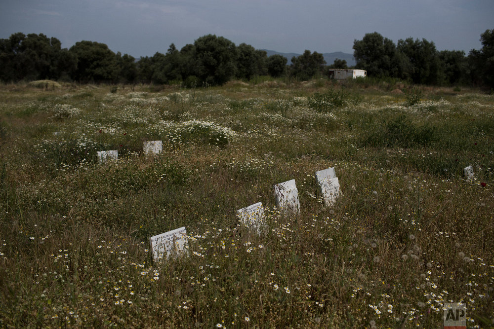 Tombstones marking the graves of migrants and refugees who drowned at sea while crossing from nearby Turkey are seen at a cemetery near the village Kato Tritos on the northeastern Aegean island of Lesbos, Greece on Saturday, May 5, 2018. (AP Photo/Petros Giannakouris)