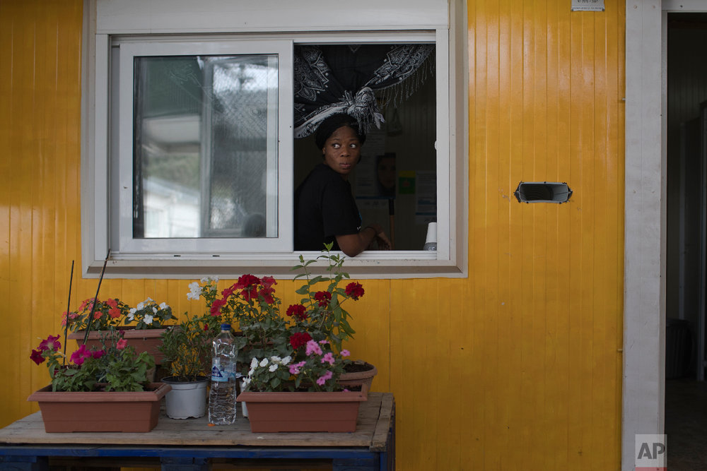 A woman looks out of a window of a prefabricated house in the sector of Moria Camp reserved to single women traveling alone in the island of Lesbos, Greece on Friday, May 4, 2018. (AP Photo/Petros Giannakouris)