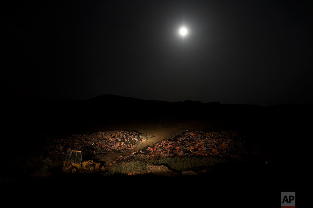 The moon rises above a huge pile of discarded life vests and dinghies used by migrants and refugees crossing from the nearby Turkish coast, at a dump on the island of Lesbos on Saturday, May 5, 2018. (AP Photo/Petros Giannakouris)