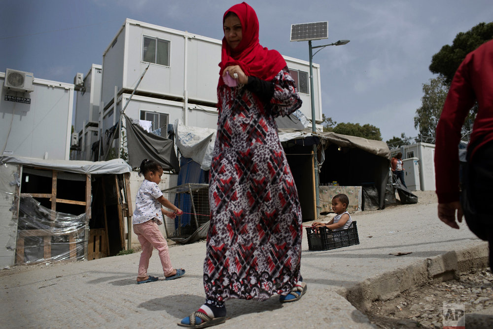 Children play as a woman walks inside the camp of Moria on the northeastern Aegean island of Lesbos, Greece on Friday, May 4, 2018. (AP Photo/Petros Giannakouris)