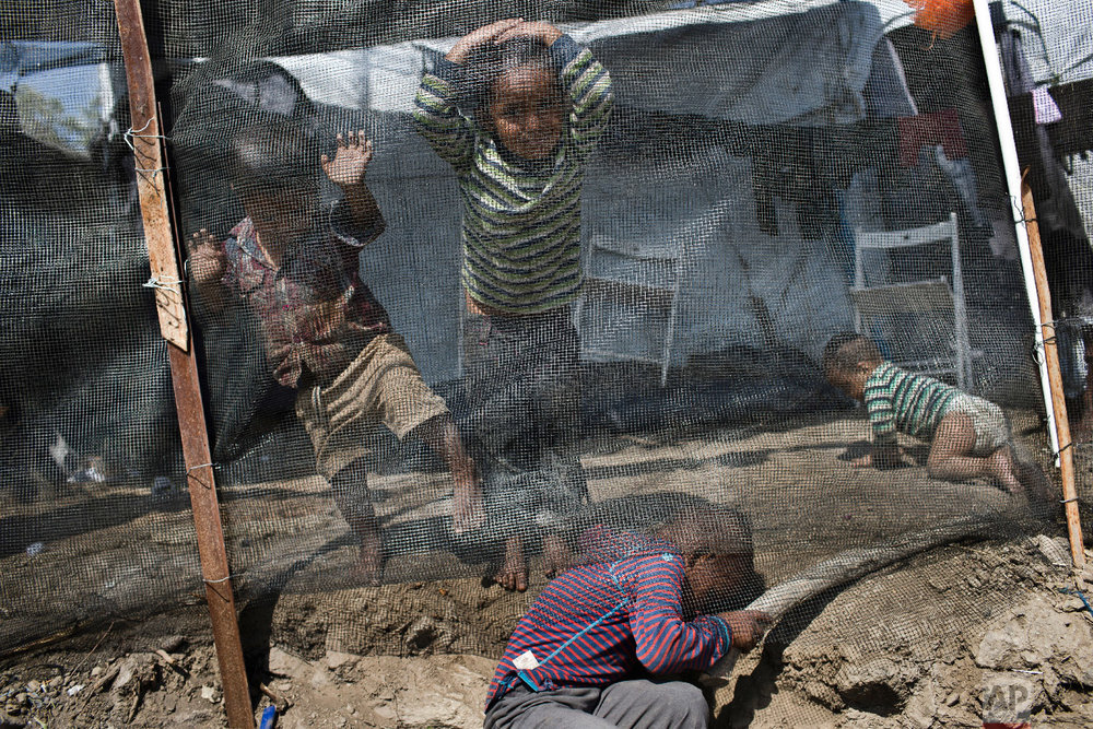 Syrian children play outside their family tent at a makeshift camp outside Moria on the northeastern Aegean island of Lesbos, Greece on Tuesday, May 2, 2018. (AP Photo/Petros Giannakouris)