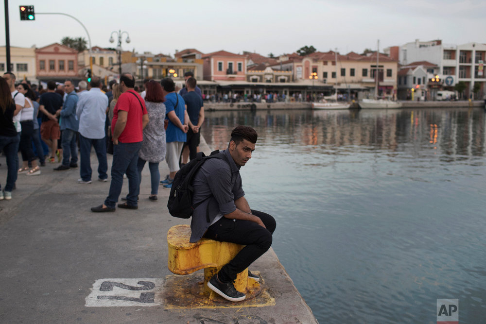 A refugee sits on a bollard in the port of Mytilene as islanders gather to protest against  the government and European Union migration policy which has left thousands of people stranded on the island on Thursday, May 3, 2018. (AP Photo/Petros Giannakouris)
