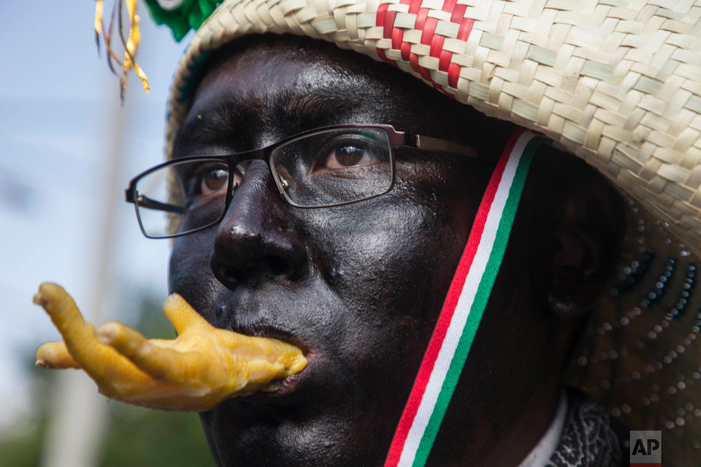 A man dressed as a revolutionary Zacapoaztla indigenous soldier holds a chicken leg snack in his mouth during a re-enactment of The Battle of Puebla between the Zacapoaztlas and French army as part of the Cinco de Mayo celebrations in Mexico City, Saturday, May 5, 2018. The holiday commemorates the victory of an ill-equipped Mexican army over French troops in Puebla on May 5, 1862. (AP Photo/Christian Palma)