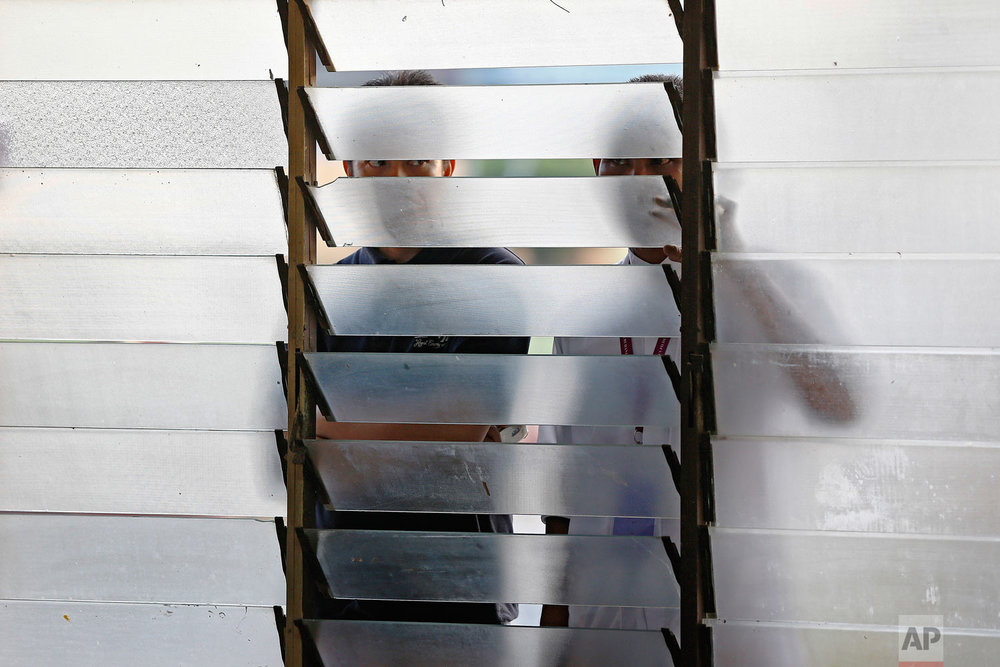Election volunteers look through a window shades as voters cast their ballots for the general elections in Alor Setar, Kedah, northern Malaysia, on Wednesday, May 9, 2018. Mahathir Mohamad was sworn in as Malaysia's seventh premier on Thursday, a day after leading his four-party opposition alliance to a stunning election victory that ousted scandal-plagued Prime Minister Najib Razak and ended his coalition's 60-year unbroken grip on power. (AP Photo/Andy Wong)