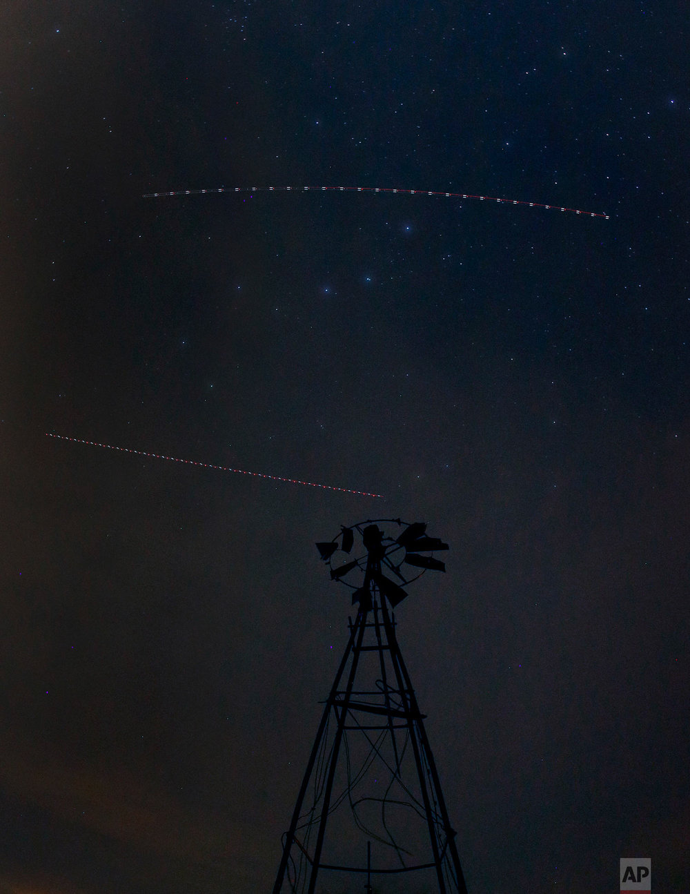In this photo made with a long exposure, an old windmill is silhouetted against the night sky with the Big Dipper constellation and trails left by the lights of two aircraft near Walker, Kan., on Friday, May 11, 2018. (AP Photo/Charlie Riedel)