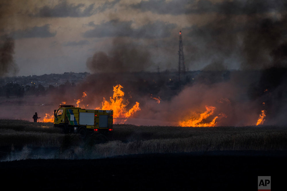 An Israeli firefighter extinguishes flames in a wheat field of the Nahal Oz kibbutz near the Israel-Gaza border on Tuesday, May 8, 2018. (AP Photo/Tsafrir Abayov)