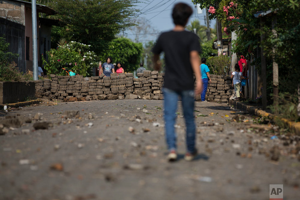 Residents walk near a road block set up by anti-government protesters in Niquinohomo, Nicaragua, on Monday, May 7, 2018, the morning after anti-government demonstrators clashed with government supporters and police. Protests in which dozens of people were killed amid a harsh crackdown by police and government-allied civilians have weakened Ortega, one of the few leftist leaders remaining in power in Latin America, forcing him to pull back on social security reforms that sparked the unrest and facing a newly emboldened opposition determined to see him leave office. (AP Photo/Moises Castillo)