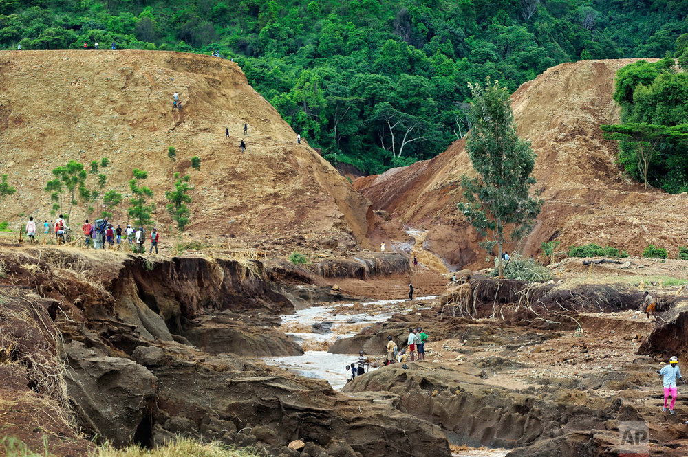 People gather in front of the broken banks of the Patel Dam near Solai in Kenya's Rift Valley, Thursday, May 10, 2018. The dam burst killing at dozens and forcing hundreds from their homes, officials said Thursday. At least 20 of the dead were children, police said. It was the deadliest single incident yet in the seasonal rains that have killed more than 170 people in Kenya since March. The floods hit as the East African nation was recovering from a severe drought that affected half of the country. (AP Photo)