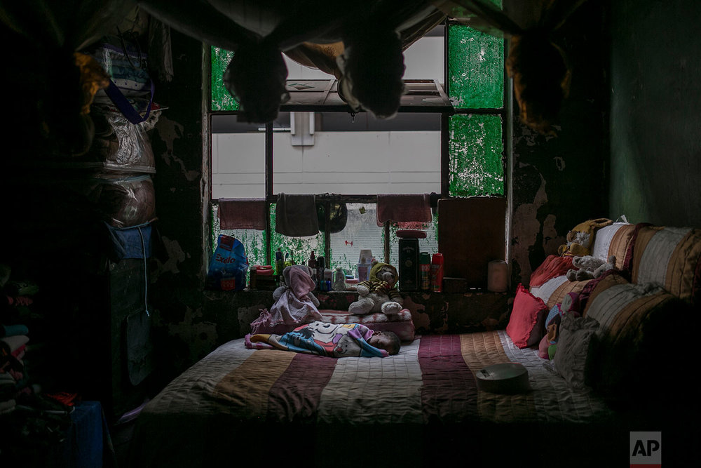 Two-year-old Makanake Angel sleeps on her mother's bed inside an abandoned building. March 30, 2018. (AP Photo/Bram Janssen)