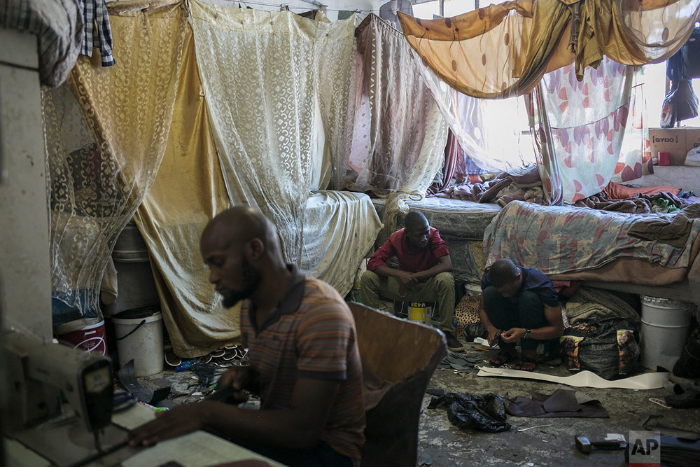 Malawian migrant shoe makers work inside their bedroom. March 29, 2018. (AP Photo/Bram Janssen)