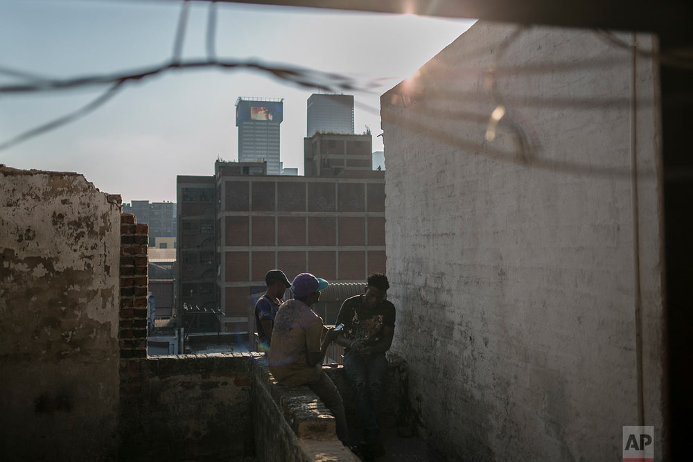 Malawian migrants sit on the rooftop of an abandoned building. March 29, 2018. (AP Photo/Bram Janssen)
