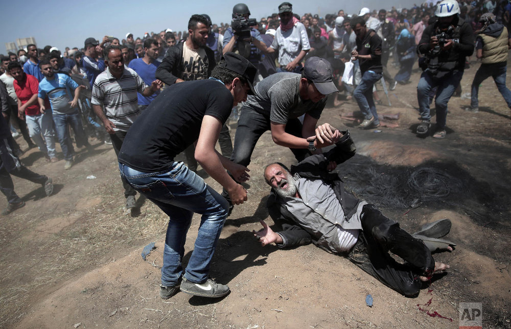 An elderly Palestinian man falls on the ground after being shot by Israeli troops during a deadly protest at the Gaza Strip's border with Israel, east of Khan Younis, Gaza Strip, Monday, May 14, 2018. (AP Photo/Khalil Hamra)