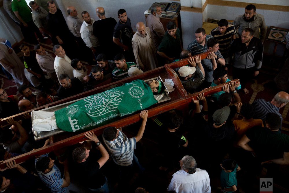Palestinians carry the body of Mousab Abu Leila, 29, during his funeral after he was killed during a protest on the border with Israel, in Gaza City, Monday, May 14, 2018. (AP Photo/Dusan Vranic)