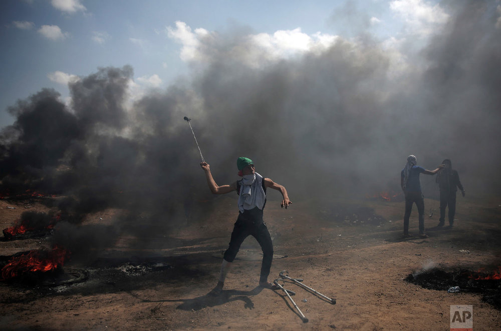 Palestinian protesters hurl stones at Israeli troops during a protest on the Gaza Strip's border with Israel, Monday, May 14, 2018. (AP Photo/Khalil Hamra)