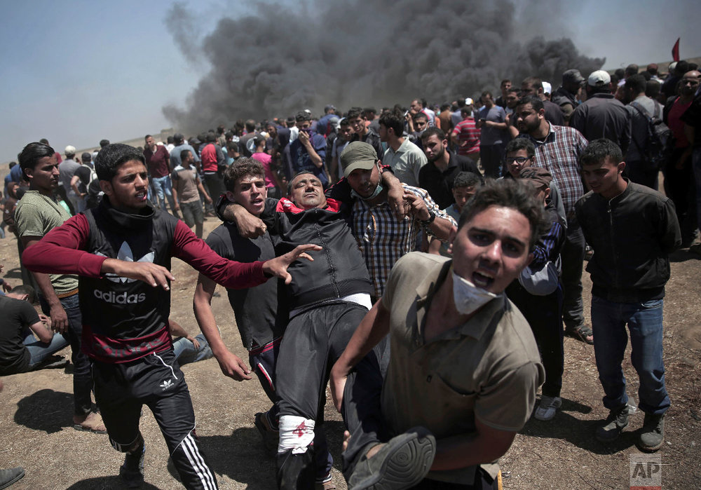 Palestinian protesters carry an injured man who was shot by Israeli troops during a deadly protest at the Gaza Strip's border with Israel, east of Khan Younis, Gaza Strip, Monday, May 14, 2018. (AP Photo/Khalil Hamra)