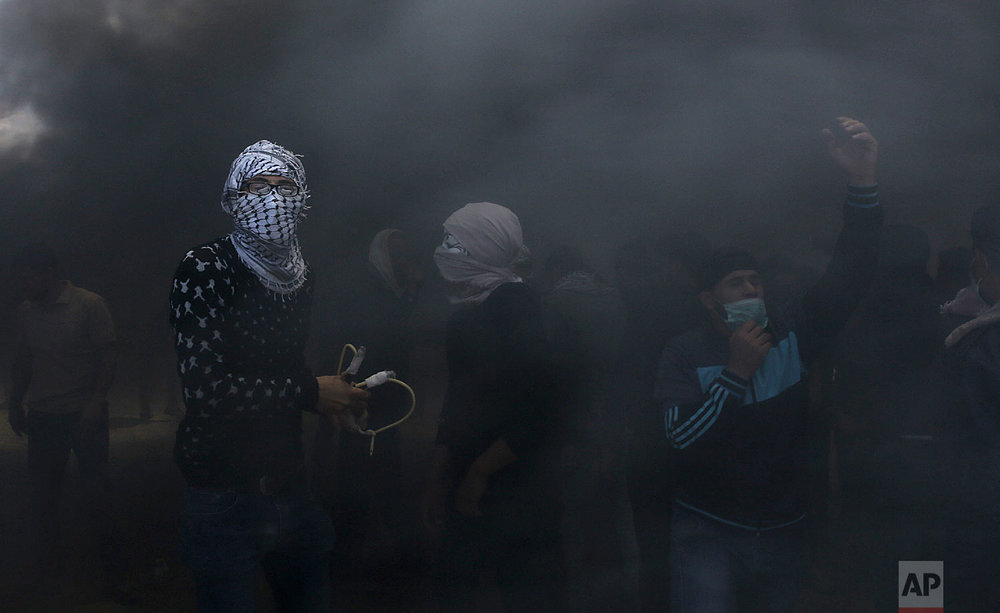 Palestinian protesters hurl stones at Israeli troops while engulfed in smoke from burning tires near the Gaza Strip's border with Israel, east of Khan Younis, in the Gaza Strip, Monday, May 14, 2018. (AP Photo/Adel Hana)