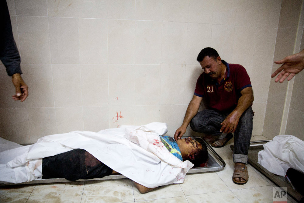A relative of a Palestinian killed during a protest on the border with Israel mourns over his body in a morgue in Beit Lahiya, Gaza Strip, Monday, May 14, 2018. (AP Photo/Dusan Vranic)