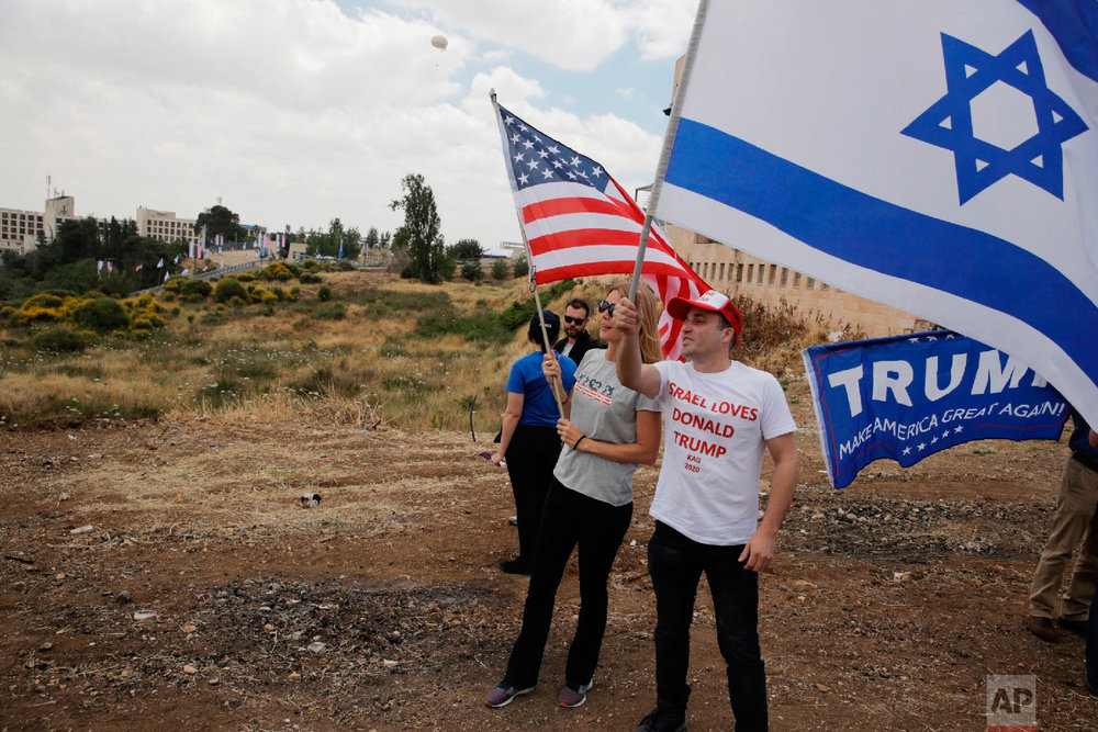 Israelis hold American and Israeli flags with the new U.S. embassy in the background in Jerusalem, Monday, May 14, 2018. (AP Photo/Sebastian Scheiner)
