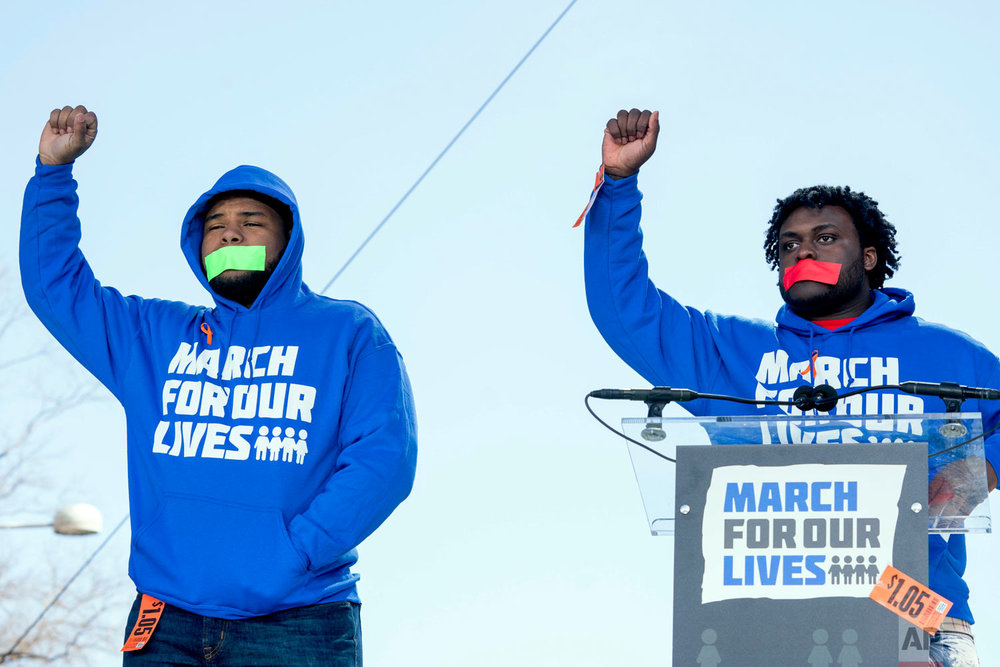 "In this Saturday, March 24, 2018 file photo, Alex King, right, and D'Angelo McDade, left, both graduating seniors at North Lawndale College Prep High School in Chicago raise their fists in the air as they arrive to speak during the ""March for Our Lives"" rally in Washington. Both are Peace Warriors at their school and both have been impacted by gun violence. King lost a 16-year-nephew last year and McDade was shot in the leg. (AP Photo/Andrew Harnik)"