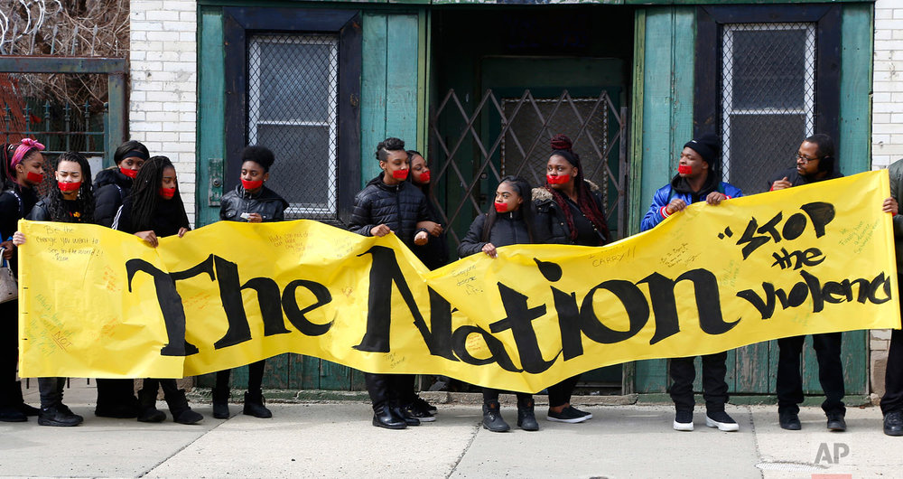 Alexis Willis, center, and other high school students from Chicago's North Lawndale neighborhood hold an anti-violence sign during a march in their neighborhood on Wednesday, March 14, 2018. Willis' 16-year-old cousin was shot and killed in Chicago three weeks after this demonstration. (AP Photo/Martha Irvine)
