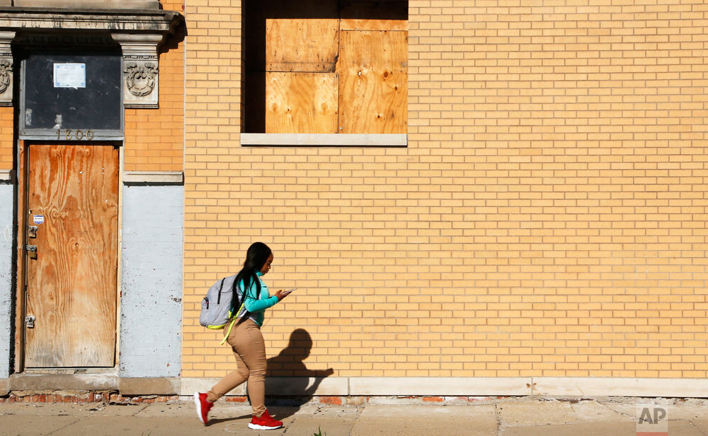 "Alexis Willis, a high school freshman, listens to music on her phone as she walks to school in Chicago's North Lawndale neighborhood on Friday, April 27, 2018. She said school shootings sadden her greatly, though she and her peers worry even more about gun violence outside of school. Her 16-year-old cousin was shot and killed in early April, causing concerns about her own safety. ""I don't want to die this summer,"" she said. (AP Photo/Martha Irvine)"