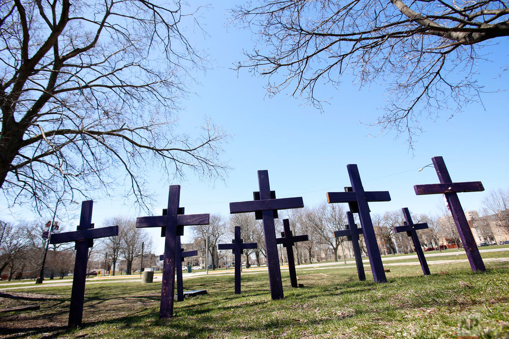 "Crosses representing victims of gun violence stand outside Collins Academy High School in Chicago's North Lawndale neighborhood on Thursday, April 19, 2018. The school is one of two campuses of North Lawndale College Prep High School. Both have Peace Warrior groups, which espouse the Rev. Dr. Martin Luther King Jr.'s ""Six Principles of Nonviolence"" in an attempt to promote peace and interrupt conflict at their schools and in their city. North Lawndale is among the Chicago neighborhoods most impacted by gun violence. Most students know someone who's been killed. (AP Photo/Martha Irvine)"