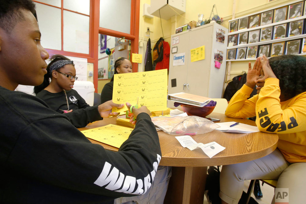 "Audrey Wright, right, quizzes fellow members of the Peace Warriors group at Chicago's North Lawndale College Prep High School on Thursday, April 19, 2018. Wright, who is a junior and the group's current president, was asking the students, from left, freshmen Otto Lewellyn III and Simone Johnson and sophomore Nia Bell, about a symbol used in the group's training on conflict resolution and team building. The students also must memorize and regularly recite the Rev. Martin Luther King's ""Six Principles of Nonviolence."" (AP Photo/Martha Irvine)"