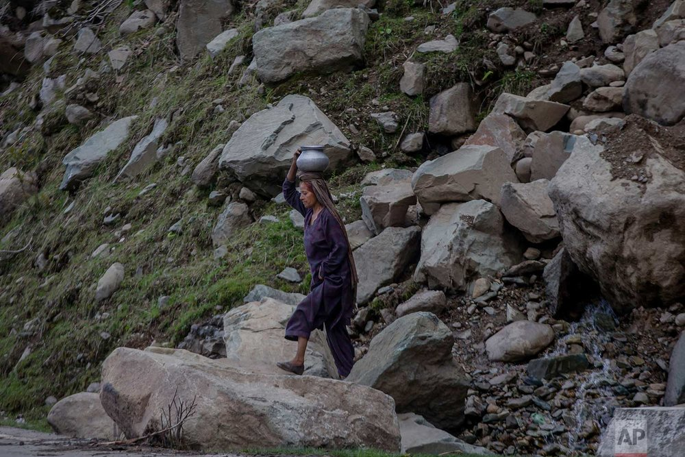 In this May 9, 2018, photo, a Kashmiri nomadic Bakarwal woman carries water after collecting it from a waterfall in Dubgan, 70 kilometers (43 miles) south of Srinagar, Indian controlled Kashmir. (AP Photo/Dar Yasin)