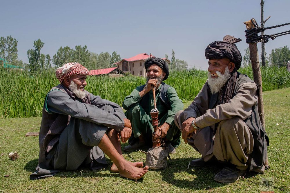 In this May 11, 2018, photo, photo, elderly Kashmiri nomadic Bakarwal men share a lighter moment as they smoke a hubble bubble or Hukka near a camp, outskirts of Srinagar, Indian controlled Kashmir. (AP Photo/Dar Yasin)