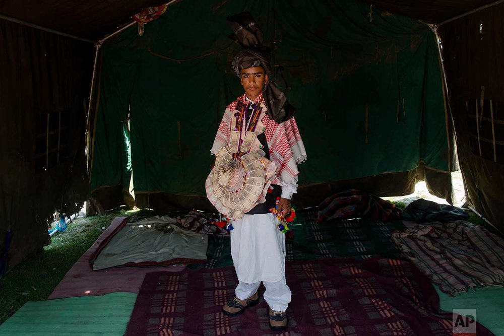 In this May 11, 2018, photo, Mushtaq Khan, a Kashmiri nomadic Bakarwal groom poses for picture inside a tent at a camps in outskirts of Srinagar, Indian controlled Kashmir. (AP Photo/Dar Yasin)