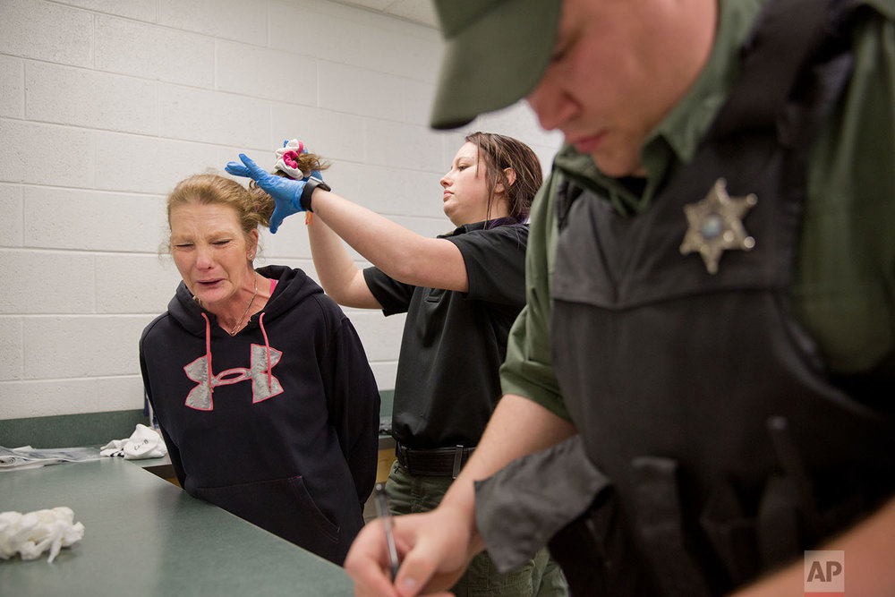 Linda Green, 51, who has struggled with drug addiction, cries as she's booked into the Campbell County Jail after being arrested on charges of public intoxication, a parole violation, in Jacksboro, Tenn., Thursday, March 29, 2018. (AP Photo/David Goldman)