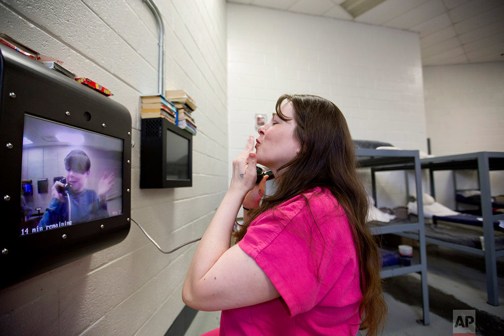 Krystle Sweat blows a kiss to her 10-year-old son Robby, during a video conference as he visits her at the Campbell County Jail in Jacksboro, Tenn., Wednesday, March 28, 2018. Robby hasn't hugged or even touched his Mom since Christmas Day 2015, just before Sweat wound up back behind bars. (AP Photo/David Goldman)