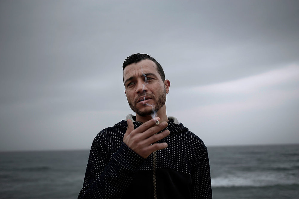 In this Saturday, April 14, 2019 photo, Ahmed Ayouby, 32, smokes a cigarette at the beach where migrants leave for Italy, in Ras Jebel, Tunisia. (AP Photo/Nariman El-Mofty)