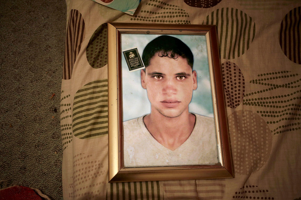 This Thursday, April 12, 2018 photo shows a framed portrait of Radya Jejli, who went missing in 2011, in his bedroom in the town of Ras Jebel, Tunisia. (AP Photo/Nariman El-Mofty)