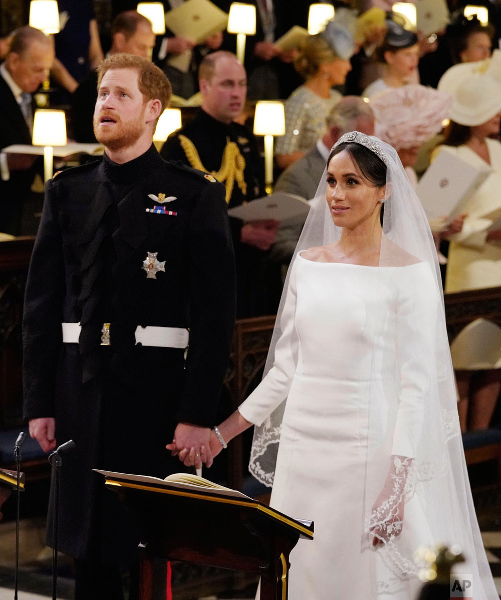Prince Harry and Meghan Markle hold hands during their wedding service at St. George's Chapel in Windsor Castle in Windsor, near London, England, Saturday, May 19, 2018. (Jonathan Brady/pool photo via AP)