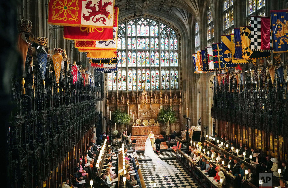 Britain's Prince Harry and Meghan Markle kneel during their wedding ceremony at St. George's Chapel in Windsor Castle in Windsor, near London, England, Saturday, May 19, 2018. (Owen Humphreys/pool photo via AP)