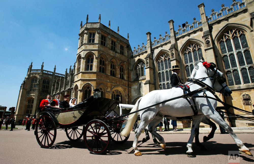 Britain's Prince Harry and Meghan Markle leave in a carriage after their wedding ceremony at St. George's Chapel in Windsor Castle in Windsor, near London, England, Saturday, May 19, 2018. (AP Photo/Alastair Grant, pool)