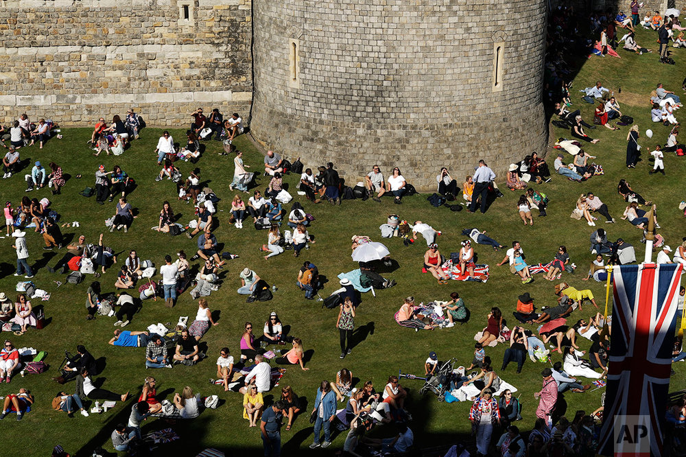 People relax on a grassy bank outside Windsor Castle after Prince Harry and Meghan Markle's wedding ceremony at St. George's Chapel in Windsor, near London, England, Saturday, May 19, 2018. (AP Photo/Matt Dunham)