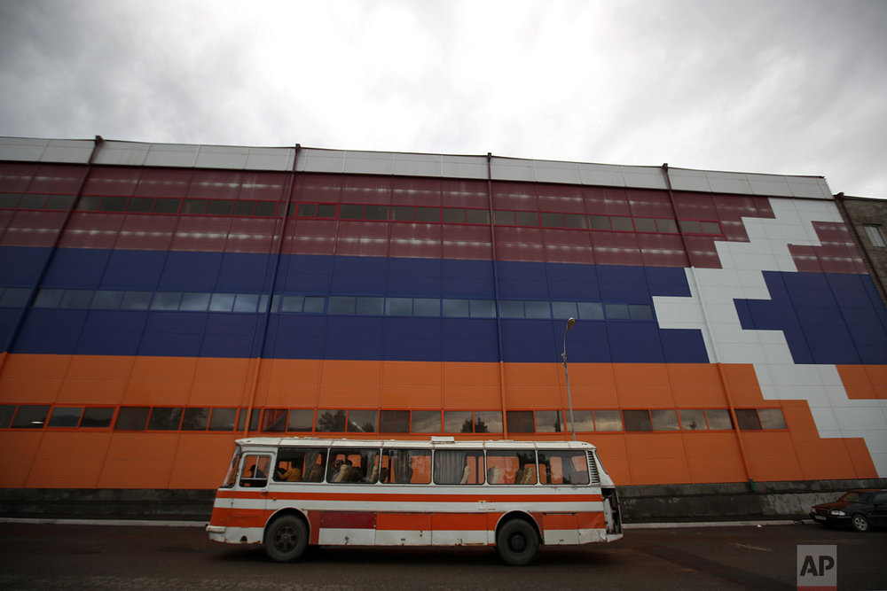 In this Thursday, May 10, 2018, a bus passes in front of a factory painted with the colors of the self-proclaimed Republic of Artsakh flag in the capital Stepanakert. (AP Photo/Thanassis Stavrakis)