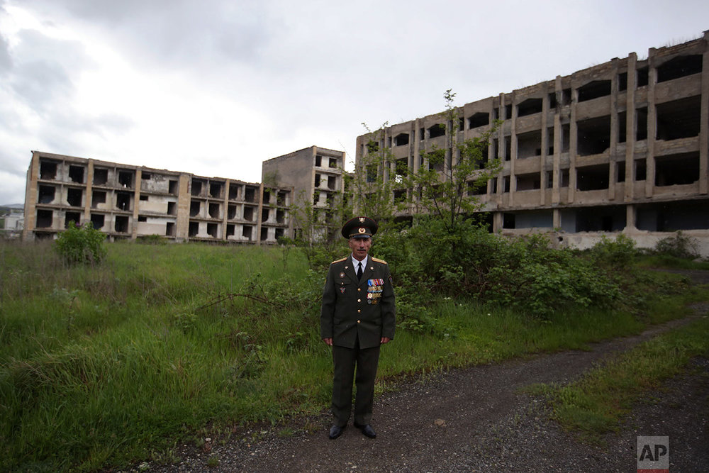 In this Thursday, May 10, 2018, Armenian Garnik Avanesyan, veteran Lieutenant Colonel poses in front of destroyed buildings during the war in Shusha town.  (AP Photo/Thanassis Stavrakis)