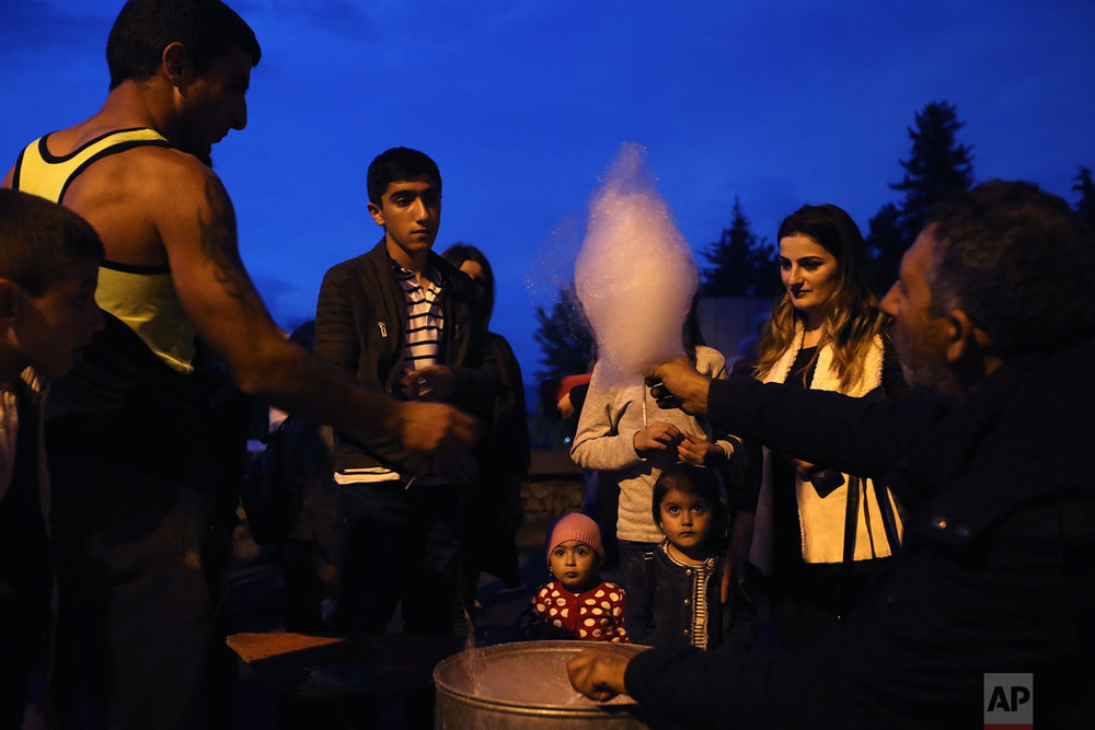 In this Wednesday, May 9, 2018, a vendor gives a candy floss in Stepanakert, during the Victory Day to celebrate 73 years since the end of WWII and the defeat of Nazi. (AP Photo/Thanassis Stavrakis)