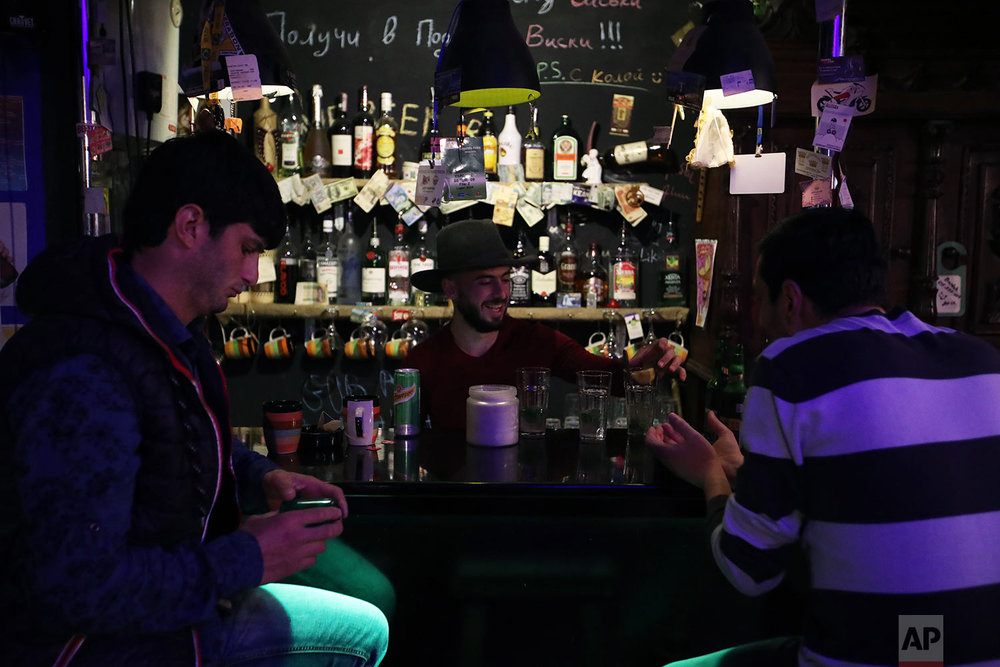 In this Thursday, May 10, 2018, Azan Grigorevich, the owner of the only rock bar in Stepanakert prepares cocktails was he speaks with his friends. (AP Photo/Thanassis Stavrakis)