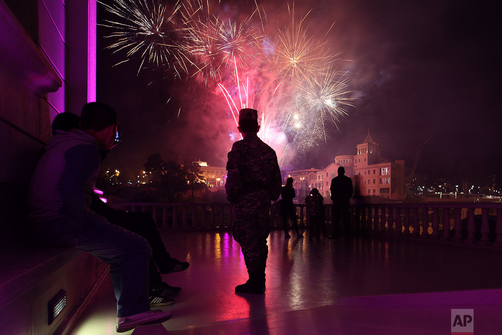 In this Wednesday, May 9, 2018, a soldier and other residents watch the fireworks in Stepanakert, during the Victory Day to celebrate 73 years since the end of WWII and the defeat of Nazi.  (AP Photo/Thanassis Stavrakis)